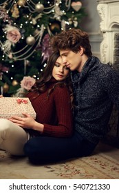Young romantic cute couple staying at home and enjoying time together. Lovers hugging in christmas decorated interior