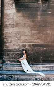 Young romantic elegant girl in long white flowy dress posing over stone ancient wall