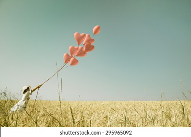 Young romantic girl with red heart balloons walking in a field of wheat.