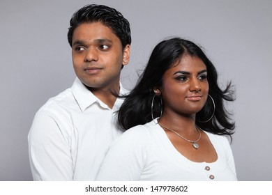 Young romantic indian couple. Wearing white shirt and jeans. Studio shot against grey.
