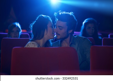 Young romantic loving couple kissing at the cinema, relationships and lifestyle concept