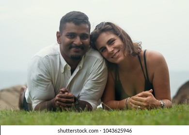 Young romantic mixed race couple lying in park on green grass. Spend free time together on holidays