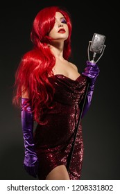 Young romantic redhead woman with very long hair in red gown with microphone on the stand on a black background. Sexy gown on a beautiful slim figure. Long pink gloves