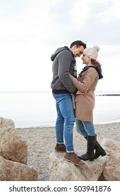 Young romantic tourist couple standing together on a rock in a beach winter holiday with coats, smiling being romantic, hugging outdoors. Travel lifestyle, seasonal living, coastal exterior.