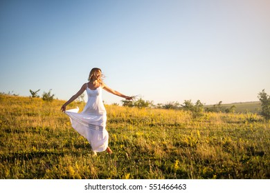 Young romantic woman on the meadow at sunset. The girl in the white dress enjoys the outdoors. Warm light