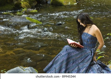 Young Romantic Woman Reading Novel in woodlands