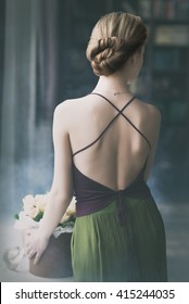 Young romantic woman staying with her back beside the window with flowers