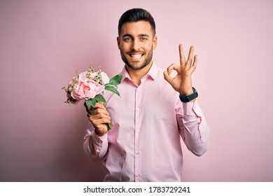 Young romatic man holding bouquet of spring flowers over pink isolatd background doing ok sign with fingers, excellent symbol