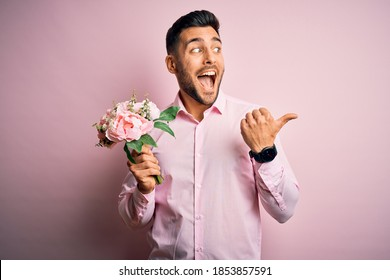 Young romatic man holding bouquet of spring flowers over pink isolatd background pointing and showing with thumb up to the side with happy face smiling