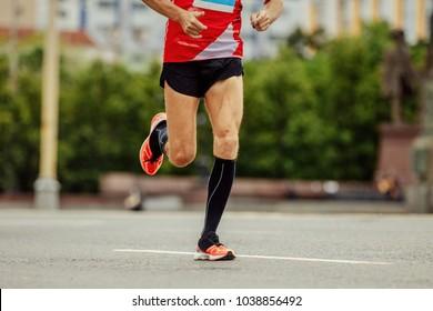 young runner in black compression socks running street in city marathon