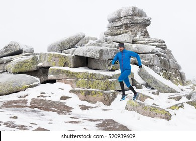 young runner in blue sportswear training running outside on the cold winter mountains trail with snow and ice