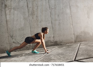 Young runner getting ready to jog forward on her daily urban workout. Concrete walls surrounding tan girl.