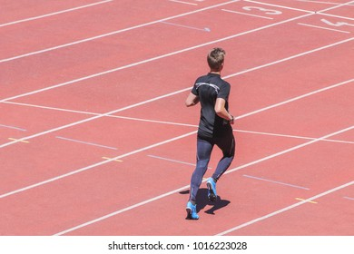 Young runner jogging on track at stadium. Running workout