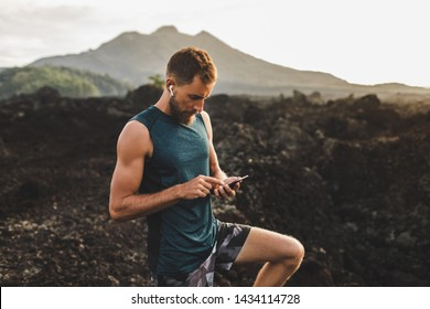 Young runner looking on training results in phone. Synchronize music with headphones air pods.