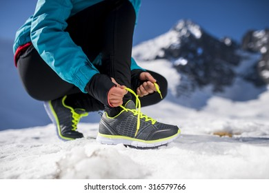 Young runner tying her shoelaces outside in winter nature