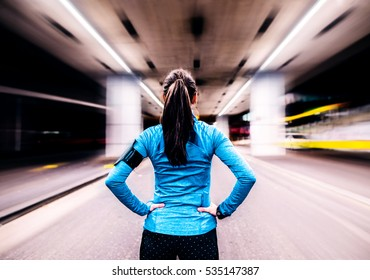 Young runner under the bridge in the evening, resting