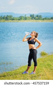 Young runner woman drinking water from the bottle, standing by the lake on sunny summer day, wearing black leggings and sports bra. Natural lighting, vibrant colors.