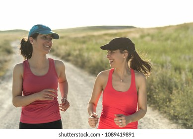 Young runner women smiling and laughing on the road