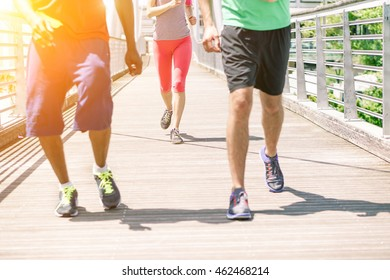 Young runners doing jogging on city contest with sunset - Multi ethnic fitness people training outdoors for sport competition - Concept of healthy lifestyle - Focus on girl's shoes