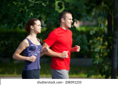 Young running couple jogging in nature