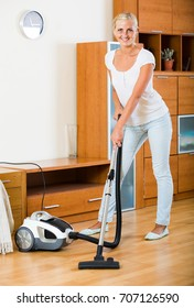 Young russian blonde in casual using domestic hoover during clean-up