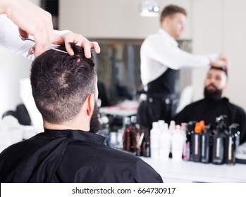 Young russian male hairdresser doing haircut for male client at hair salon