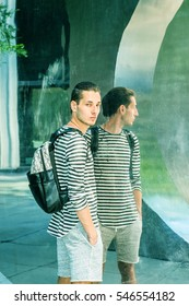 Young Russian Man with hipster hair, wearing striped long sleeve T shirt, shorts, shoulder carrying back bag, standing by metal mirror, looking away, going to travel. Color filtered effect