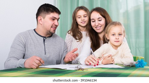 Young russian  parents with little children buying insurance and smiling