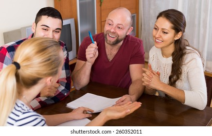 Young russian spouses sitting with documents and asking friends for advice