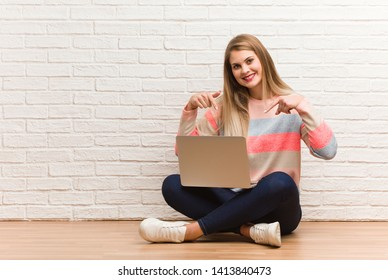 Young russian student woman sitting pointing to the bottom with fingers