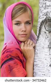 Young russian woman in headscarf near birch