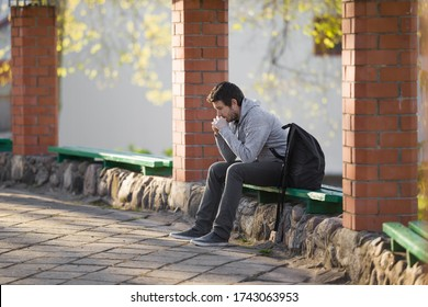 Young sad adult man sitting alone on wooden bench. Thinking about life. Side view.