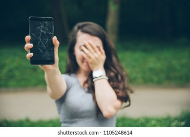 young sad adult woman showing cracked phone