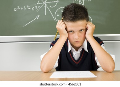 Young, sad boy sitting at desk over piece of paper with pencil in hand. Looking at camera, front view