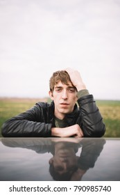 young sad boy with an unusual appearance posing near the car in the summer field. emotional portrait: long hair and crooked teeth. street style: jeans and a light jacket. Wallpaper for desktop