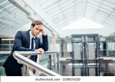 Young sad businessman covering his face with his hand. Man got bad news.Stress