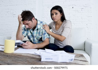young sad couple at home living room couch calculating monthly expenses worried in stress with bank papers and documents in paying taxes , mortgage debt and cost of living concept