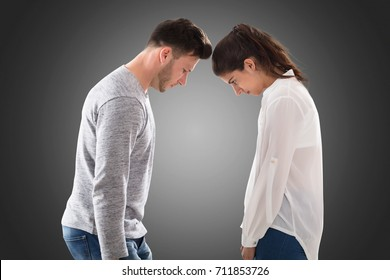 Young Sad Couple Standing Face To Face On Gray Background