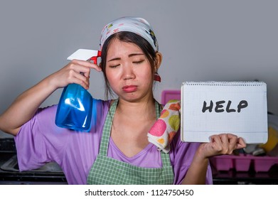 young sad and depressed Asian Korean woman holding help sign and spray cleaner bottle feeling stressed and frustrated working at home kitchen in housekeeping routine stress concept