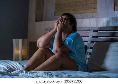 young sad and depressed fat and chubby Asian girl feeling upset and desperate crying on bed at home victim of bullying and discrimination for her plus size and overweight far from standards