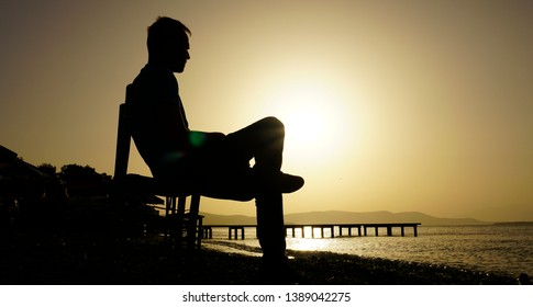 Young sad depressed man sit alone on chair, looking at distant sea / seascape horizon. Time to go, say goodbye. Miss someone. Desire, hope to go far away. Unhappy boy feel lonely at seaside outdoor.