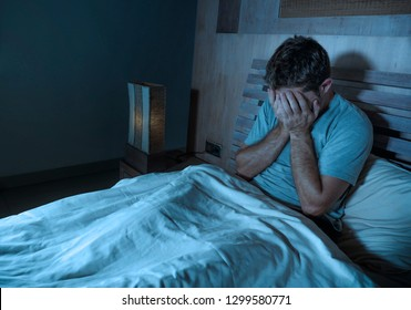 young sad and depressed sleepless man lying on bed worried and thoughtful at home bedroom suffering depression problem feeling unwell and desperate  broken heart after relationship divorce