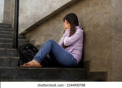 young sad and depressed student woman or bullied teenager girl sitting outdoors on street staircase scared and anxious victim of bullying feeling desperate suffering depression problem