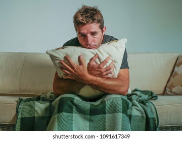 young sad and desperate man at home sitting at living sofa couch holding pillow suffering depression and stress worried about problem feeling miserable in depression lifestyle concept