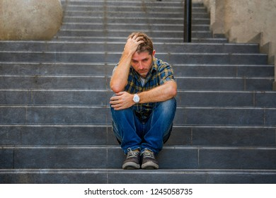 young sad and desperate man sitting outdoors at street stairs suffering anxiety and depression feeling miserable crying abandoned in unemployment and broken heart concept