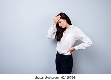 Young sad female worker touching her forehead because of having a headache after a long working day