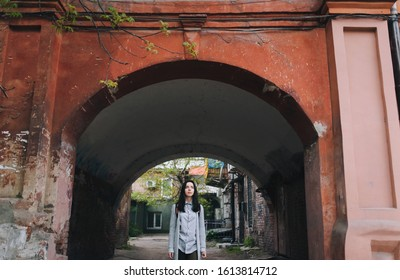 A young sad girl in a gray cardigan and a shirt stands in the arch of an old slum yard and looks at the viewer. The concept of poverty, decline and lack of prospects.