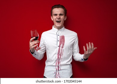 young sad guy in a white shirt spilled red wine on himself on a red background, an angry man put a stain of wine on his clothes