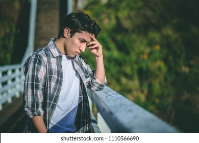 Young sad looking man on a bridge with depression thinking about suicide