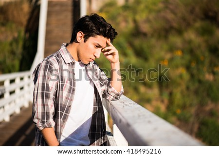 Young sad looking man standing on a bridge, contemplating suicide; crisis, problems, desperation